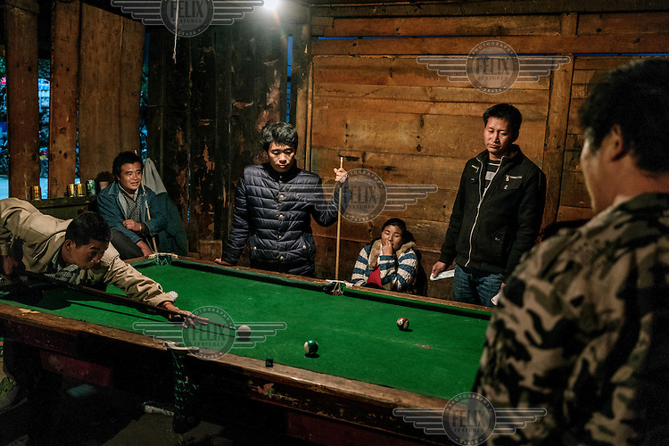 Local youngsters play pool and gamble in a bar.
