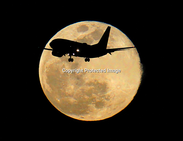 Airline jet was silhouetted by March's full moon as seen from SFO.