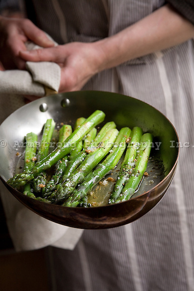 Cook holding a copper-bottomed pan with sauteed asparagus