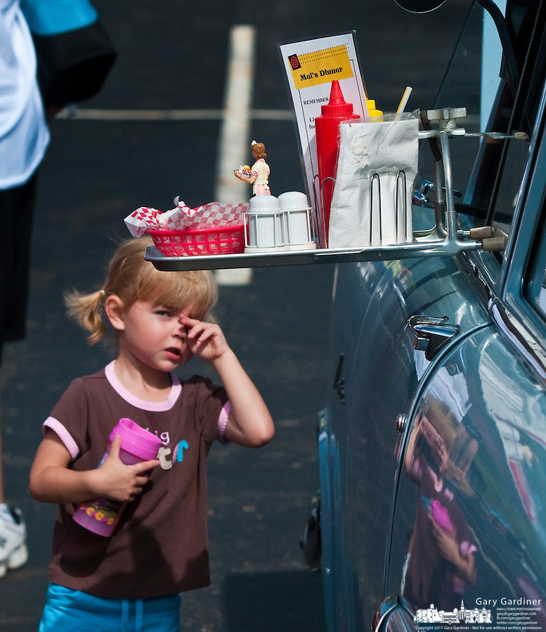 A young girl looks at a food tray hanging from the window of an antique car on display at the Westerville Church of the Nazarene's 3rd Annual Community Car Show.
