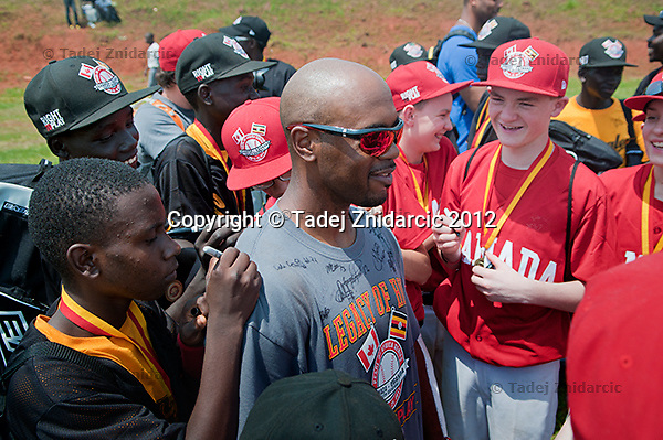 Ugandan and Canadian players sign the shirt of Philadelphia Phillies shortstop Jimmy Rollins after the game in Mpigi, Uganda on January 17 2012 between Ugandan Little League team and Canadian Little League team from Langley.