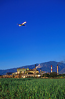 A commerical flight on final approach over the Puunene Sugar Mill, Maui's last remaining sugar mill and the world's first computer controlled sugar factory. Sugarcane in the foreground and the West Maui Mountains in the distance.
