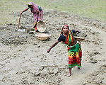 In order to raise her home a few inches, Shosida Begum (right) carries dirt in a basket in West Fasura, a village on an island in the Brahmaputra River in northern Bangladesh. Severe flooding in August 2017 destroyed the island's crops but RDRS Bangladesh, a member of the ACT Alliance, provided emergency cash grants to vulnerable island families so they could reestablish their household economies and restart their lives.