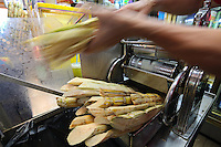 Crushing sugar cane for a sugar cane juice Maxwell Food Centre in Singapore.  Located in the heart of Chinatown, Maxwell Road Hawker Centre has over 100 stalls, providing one of the biggest varieties of local food in Singapore