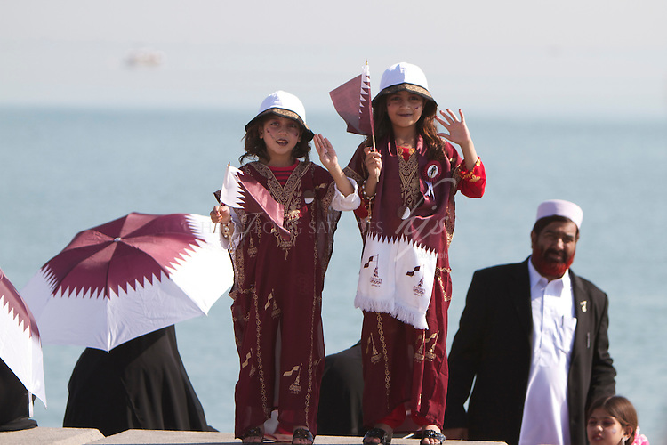 Two lovely local girls in their national costume, happily smiling to people passing by! Doha, Qatar | Dec 10