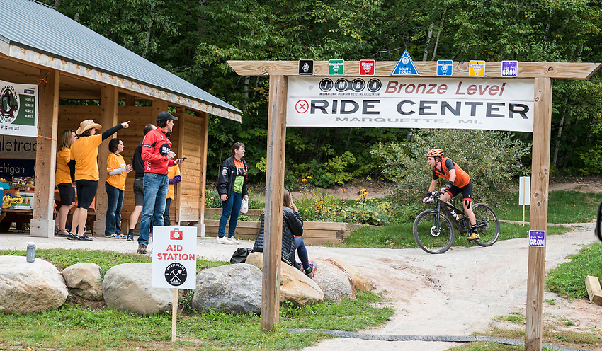 Bikers pass through the NTN South Trails Trailhead aid station during the Marji Gesick 100 endurance race in Marquette County, Michigan.
