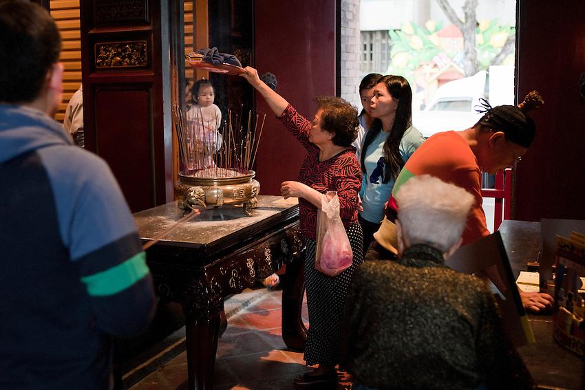 Cérémonie de bénédiction dans le temple de Xindian en pleine journée. Les habitants de Taipei viennent déposer une assiette remplie d'aliments et même des vêtements que le moine taoïste va bénir et leur rendre. Après avoir fait tourné trois fois l'assiette  au dessus de l'encens consacré il leur faudra porter les vêtements bénis et manger les aliments pour que la bénédiction soit effective.