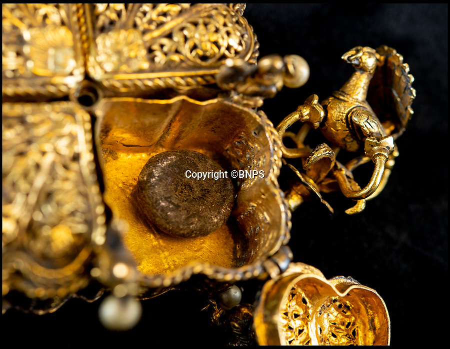 BNPS.co.uk (01202) 558833<br /> Pic: PhilYeomans/BNPS<br /> <br /> The peacock lock revealed 220 year old betel nuts. Tipu Sultan's ornate solid gold betel nut casket.<br /> <br /> Stunning artefacts from Indian hero Tipu Sultan's fateful last stand have been rediscovered by the family of an East India Company Major who took part in the famous battle that ended his reign.<br /> <br /> And now Major Thomas Hart's lucky descendents are likely to become overnight millionaires after retrieving the historic items from their dusty attic.<br /> <br /> The fascinating treasures were taken from Tipu's captured fortress of Seringapatam in the wake of his defeat by British forces led by a young Duke of Wellington in 1799.<br /> <br /> The cache of ornate gold arms and personal effects even include's the battle damaged musket the Sultan used in his fatal last stand against the expanding British Empire in India.<br /> <br /> Tipu was last seen on the battlements of the fortress firing his hunting musket at the advancing British and after the fierce encounter his body was found bearing many wounds, including a musket ball shot above his right eye.<br /> <br /> The rediscovered musket, complete with battle damaged bayonet, has the distinctive tiger stripe pattern unique to the self styled Tiger of Mysore own weapons - and tellingly there is also shot damage to the lock and stock that may have been caused by the musket ball that finished him off.<br /> <br /> Also included in the sale are four ornate gold-encrusted sword's bearing the mark of Haider Ali Khan, Tipu's father and the previous ruler of independent Mysore, along with a solid gold 'betel casket' complete with three 220 year old nuts still inside.<br /> <br /> The war booty was brought back to Britain by Major Thomas Hart of the British East India Company following the fourth and final Anglo-Mysore war.<br /> <br /> They have been passed down through the family ever since and now belong to a couple who have kept them wrapped in newspaper in the dusty attic of their semi-detached home for years.