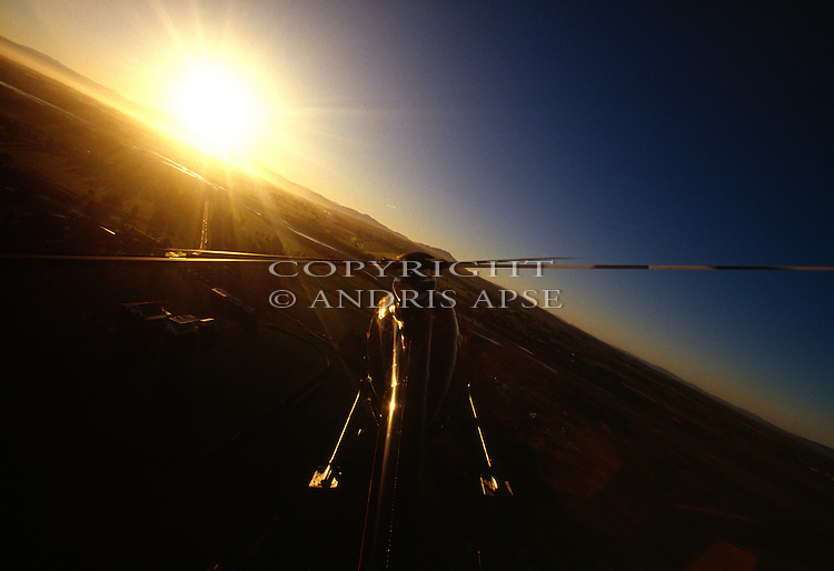 Hughes 500 D Helicopter flying abover the  Canterbury  Plains at sunrise New Zealand