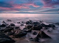 Rocky shore and sunrise. with Kaho'olehu Island. Maui, Hawaii