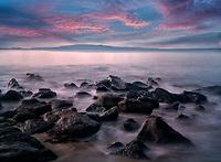 Rocky shore and sunrise. with Kaho'olehu Island. Maui, Hawaii