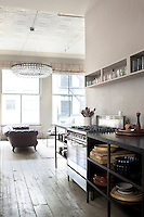 Steel shelving topped with black granite flanks an industrial range in the open plan kitchen/living area