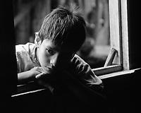 Boy peeking through window in Iquitos Peru.
