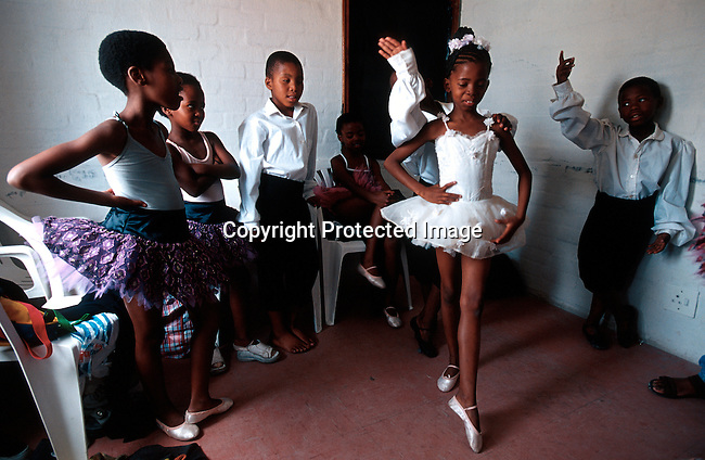 "Wongi Zoe (center), age 8, in her dressing room warming up on November 25, 2000 before a yearly performance in Guguletu a poor township outside Cape Town, South Africa. These kids are dancing in the 'Dance for All"" programme, run by the Cape town city Ballet. It gives unpriviliged children a chance to explore dance and music..Photo: Per-Anders Pettersson (ppettersso@aol.com)"