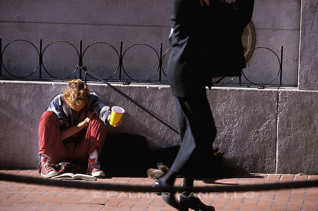 A well dressed woman walks by a homelss youth with outstretched change cup