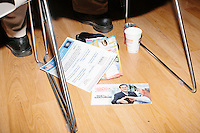 Campaign materials lay on the ground under an audience members' seat as former Pennsylvania senator and Republican presidential candidate Rick Santorum speaks to an audience at the Concord office of New England College in Concord, New Hampshire.