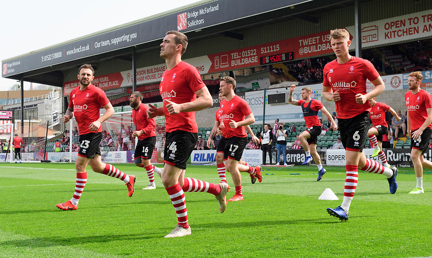 Lincoln City's Neal Eardley, left, with team-mates Harry Toffolo, centre, and Mark O'Hara during the pre-match warm-up<br /> <br /> Photographer Chris Vaughan/CameraSport<br /> <br /> The EFL Sky Bet League Two - Lincoln City v Tranmere Rovers - Monday 22nd April 2019 - Sincil Bank - Lincoln<br /> <br /> World Copyright © 2019 CameraSport. All rights reserved. 43 Linden Ave. Countesthorpe. Leicester. England. LE8 5PG - Tel: +44 (0) 116 277 4147 - admin@camerasport.com - www.camerasport.com