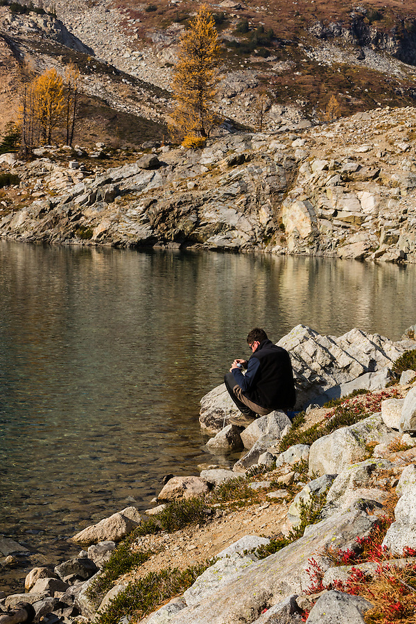 A young man in his 20's pumps water for hydration out of Wing Lake in Washington's North Cascade Mountains next to a yellow western larch tree in October.