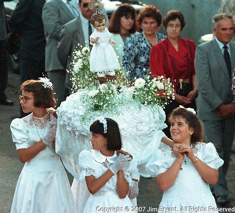 Young girls, who will take their First Communion, carry a statue of the Virgin Mary during during a religious parade honoring the festival Divino Espirito Santo, which begins on Pentecostal Sunday and last till the end of Summer on Terceira, Azores. Far out in the Atlantic Ocean, some 850 miles off the western coast of Lisbon, Portugal lies the 425-mile long archipelago of the Azores. (Jim Bryant Photo).......