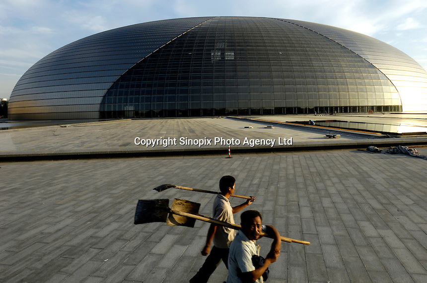 Two workers walk past the National Grand Theatre designed by French architect Paul Andreu, beside the Great Hall of the People in Beijing, China..27 Aug 2007