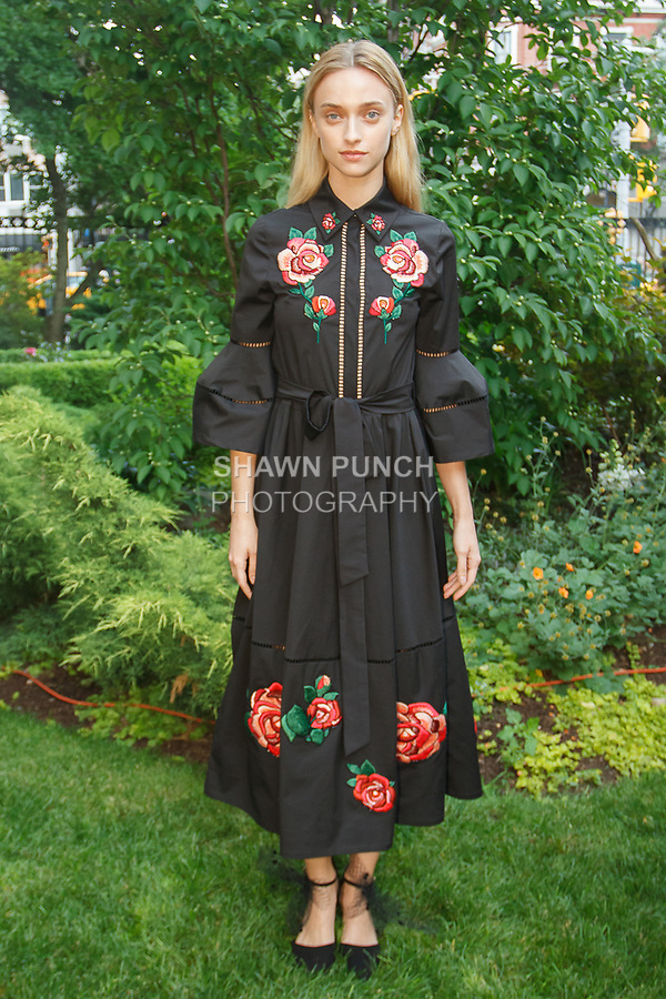 """Model poses in a black cotton poplin shirtdress with embroidered rose tattoo detail, from the Lela Rose Resort 2018 """"Garden Party"""" collection in Jefferson Market Garden on June 7 2017, during Resort Fashion Week in New York City."""