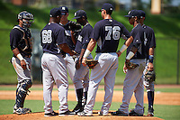 GCL Yankees 1 manager Julio Mosquera (68) talks with pitcher Anderson Severino (68) as catcher Jerry Seitz, Donny Sands, Wilkerman Garcia, Bryan Cuevas and Victor Rey (76) listen in during the first game of a doubleheader against the GCL Tigers on August 5, 2015 at Tigertown in Lakeland, Florida.  GCL Tigers derated the GCL Yankees 5-2.  (Mike Janes/Four Seam Images)