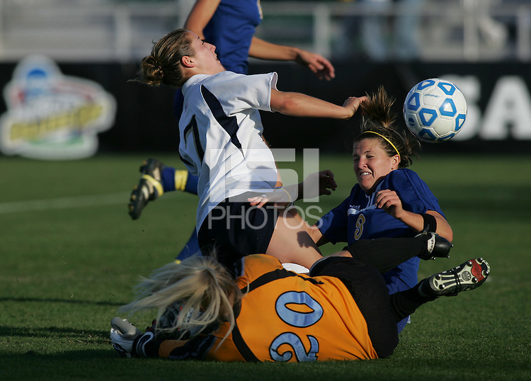 05 December,  2004.   Notre Dame forward  Candace Chapman (8) collides with UCLA's Kim Devine (3) and goalkeeper Valerie Henderson (20) during the NCAA finals at SAS Stadium in Cary, NC.