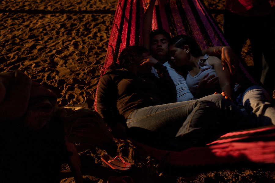 Barra Vieja, Mexico, February 19, 2012 - Three students sleep in a hammock on the beach at Campamento Tortuguera, an organization that works to save the turtles from human predators. The students are there as part of a work study program. <br /> <br /> Leatherbacks are one of the more endangered species, mostly due to human activity, including being caught in fishing nets, ingestion of plastic and trash, and illegal egg collection. The latter is a considerable problem in Mexico despite laws enacted in 1991 protecting the turtles.
