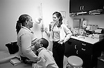 Young female internal medicine resident physician speaking and gesturing to middle age African-American female sitting on examination table. Young male child hugs mother and looks up from below