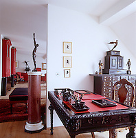 In the study an antique Chinese chest topped with bronze figurines is used as a filing cabinet adjacent to the ornately carved desk and chair