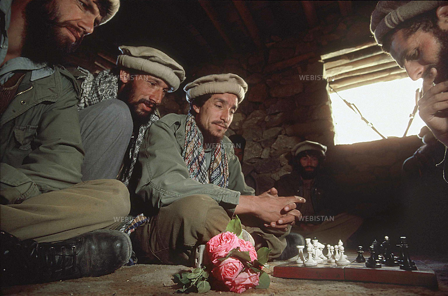 Afghanistan. Panjshir Valley. 1985. Commander Massoud (1953-2001) plays chess with a group of Mujahideen during the Soviet invasion of Afghanistan (1979-1989). <br /> <br /> Afghanistan. Vall&eacute;e du Panjshir. 1985. Le commandant Massoud (1953-2001) joue aux &eacute;checs avec un groupe de Moudjahidin pendant la guerre d'Afghanistan (1979-1989).