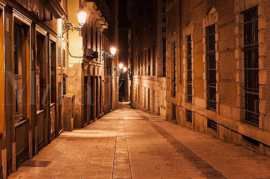 Narrow alley illuminated by street lamps at night, Madrid, Spain
