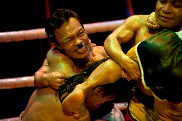 As the midgets slide around the ring customers, both tourists and locals, look on and laugh.<br /> <br /> In the red light area of Manila's Makati district, customers who've had enough of dancing girls have another form of exploitation to amuse them: midget oil wrestling.