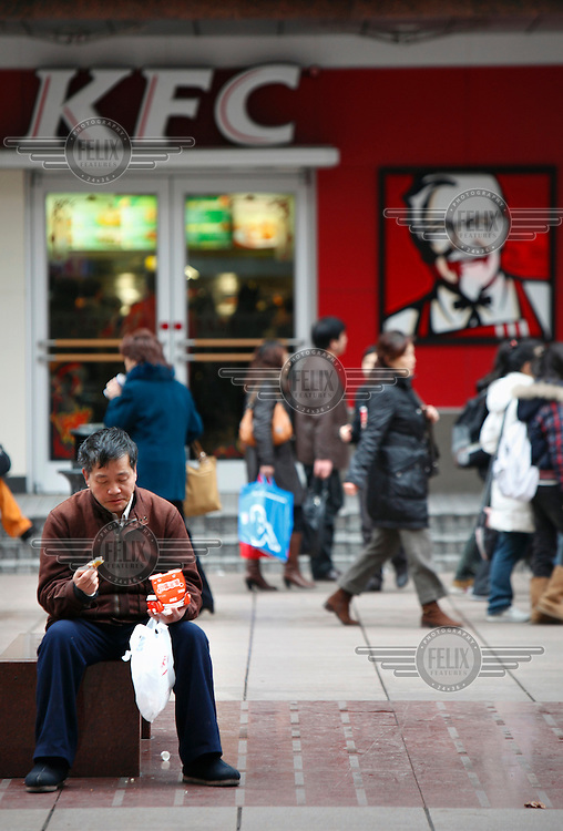 A man, sitting outside a KFC fast food restaurant, eating a snack. Yum! Brands Inc, the parent company of KFC, has more than 3, 200 branches in China and is often cited as the most successful foreign business in China. ..