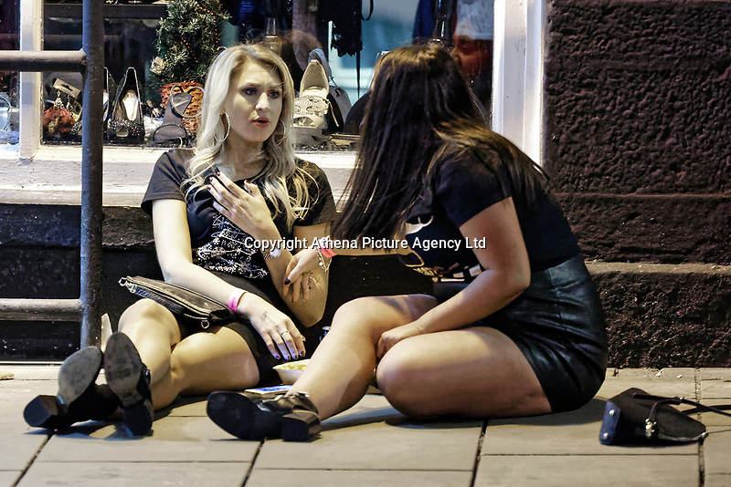 Pictured: Two women sit on the pavement. Friday 14 December 2018<br /> Re: Revellers in Wind Street, Swansea, Wales, UK.