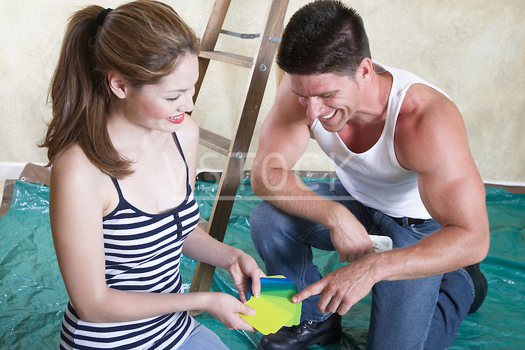 Couple looking at color samples in drop cloth covered room