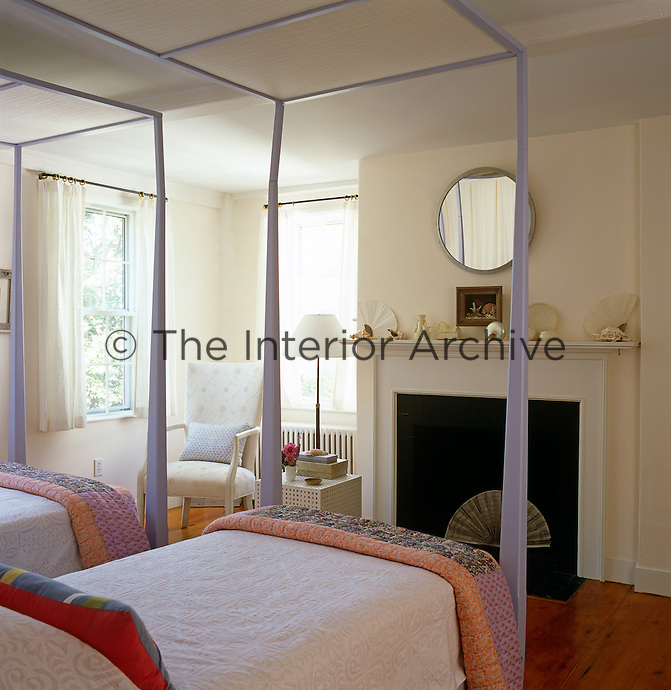 Twin four-poster beds painted a pale lavender in a simple airy bedroom