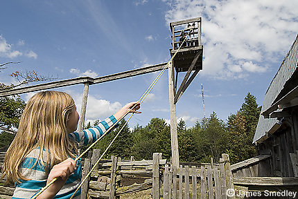 Young girl working a contraption at an historic farm