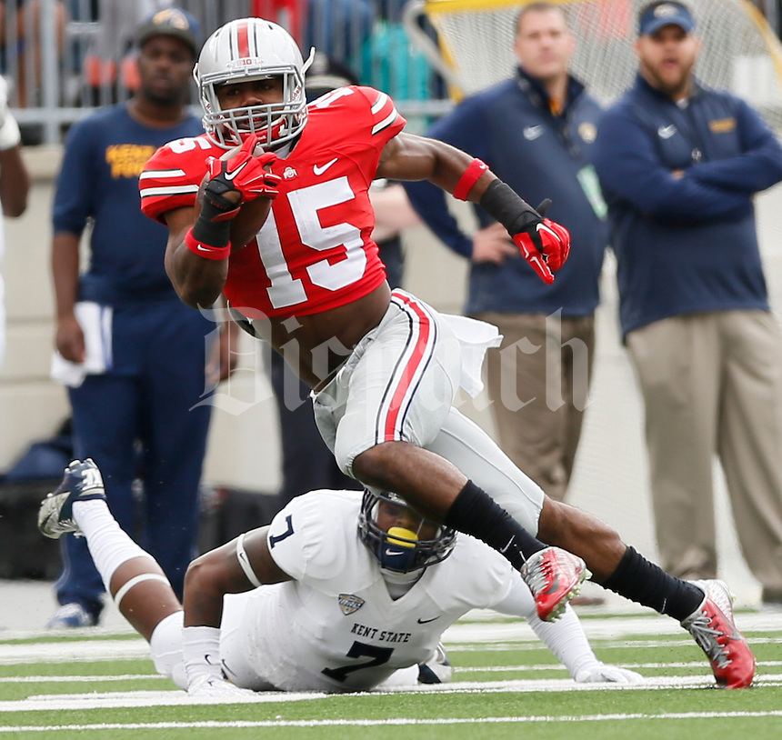 Ohio State Buckeyes running back Ezekiel Elliott (15) dodges Kent State Golden Flashes safety Elcee Refuge (7) during Saturday's NCAA Division I football game at Ohio Stadium in Columbus on September 13, 2014. (Dispatch Photo by Barbara J. Perenic)