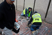 Pablo Mendez (center) and Jimmy King repair a brick sidewalk for the Boston Public Works Department in Boston, Massachusetts, USA, on April 12, 2012.  The city uses a computer system to track public complaints and record work done by city crews to mitigate these complaints.  A supervisor or inspector photographs before and after pictures of the work in addition to making notes about the work done.