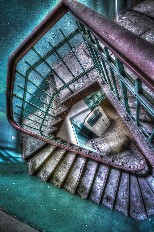 Looking down an old stairwell to an open door in a derelict asylum
