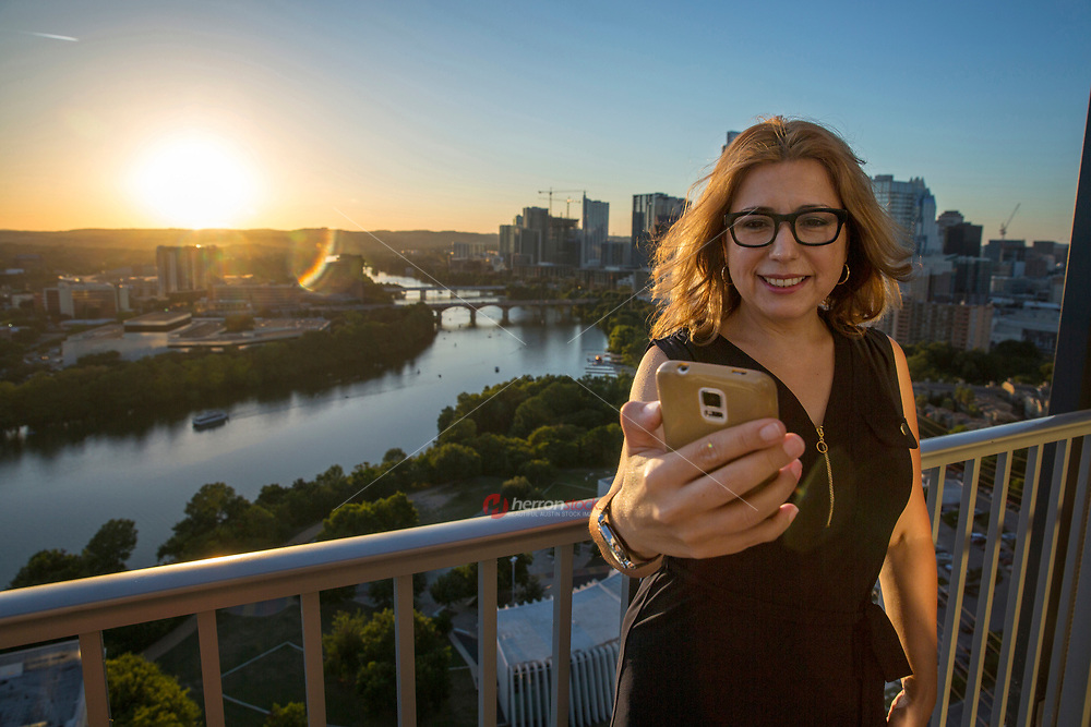Smiling, attractive woman wearing glasses in casual dress taking selfies on high-rise skyscraper balcony, Austin, Texas skyline backdrop at sunset.