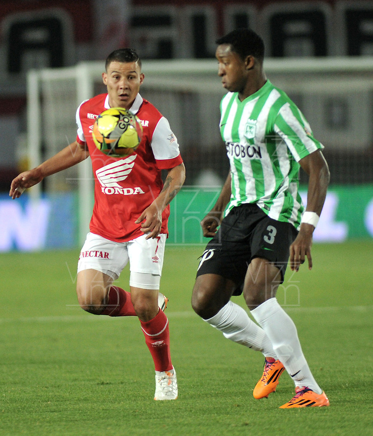 BOGOTA - COLOMBIA -07 -05-2014: Luis Arias (Izq.) jugador de Independiente Santa Fe disputa el balón con Oscar Murillo (Der.) jugador de Atletico Nacional, durante partido de ida entre Independiente Santa Fe y Atletico Nacional, por las semifinales de la Liga Postobon I-2014, jugado en el estadio Nemesio Camacho El Campin de la ciudad de Bogota./ Luis Arias (L) player of Independiente Santa Fe struggles for the ball with Oscar Murillo (R) player of Atletico Nacional, during a match for the first leg between Independiente Santa Fe and Atletico Nacional, for the semifinals of the Liga Postobon I -2014 at the Nemesio Camacho El Campin Stadium in Bogota city, Photos: VizzorImage  / Luis Ramirez / Staff.