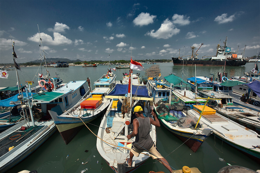 Indonesia - Bangka Island - Sungai Liat harbour - Fishing boats parked in the harbour. The killing of coral reefs caused by tin mining have harmed fishermen livelihood, by pushing fish stock far away from the coast. Fishermen complain that, while before they were able to fish within four miles from the coast, now they have to go as far as 17 miles where waves are much higher and it is more dangerous to work.