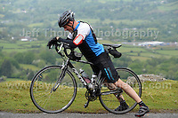 Competitors climb the challenging iconic and notorious 6km 10% stretch of road namely The Tumble during the Wales Velothon 2016 140km route cycling race. Stretching the calves.  <br />