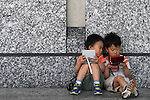 """May 9, 2010 - Tokyo, Japan - Two Japanese boys play Nintendo's portable video game 'DS' in front of the official Pokemon store in Tokyo on May 9, 2010. Nintendo recently announced that the DS handheld device had become the best selling gaming handheld of all time, with a total of 129 million units sold. The DS 'family' have surpassed the """"Game Boy"""" series which hit 118 million over two decades."""