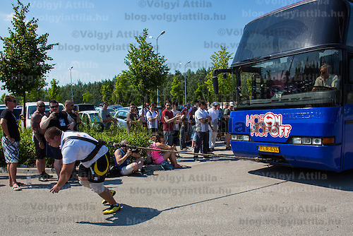 Peter Puzser of Slovakia competes in bus pulling during the Giants Live Strongman Competition in Budapest, Hungary on June 17, 2012. ATTILA VOLGYI