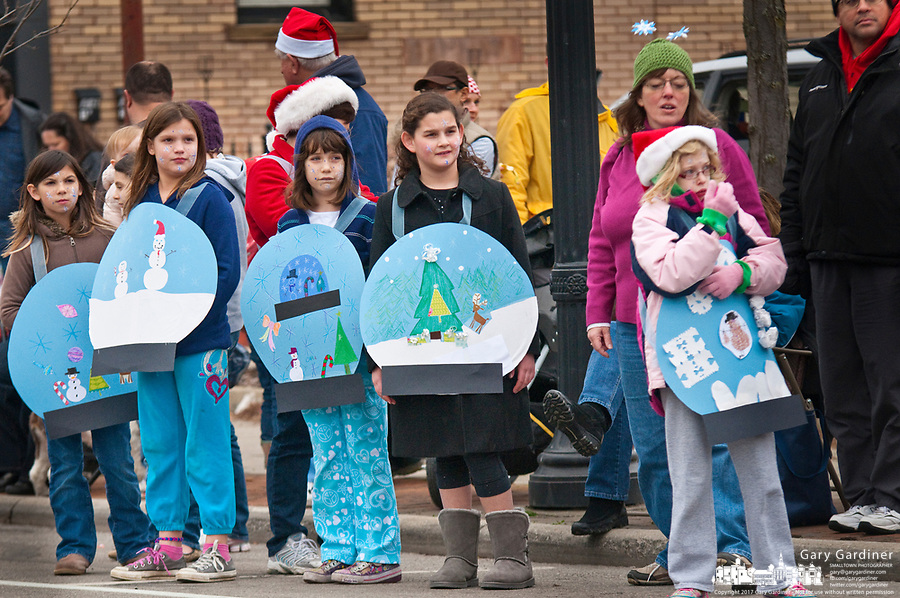 Children wearing Christmas ornament banners stand along the Christmas Parade route waiting for the arrival of Santa at the end.
