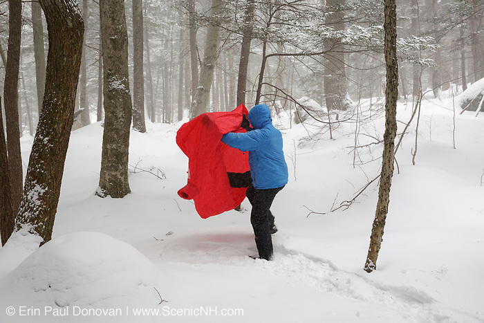 A hiker prepares to use the Bothy 2 during the winter months in the White Mountains of New Hampshire USA. The Bothy 2 is a light-weight two man emergency shelter made by Terra Nova Equipment.