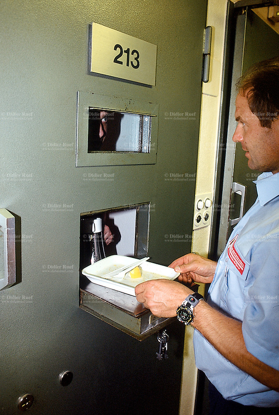 Switzerland. Bern. Regionalfgefängnis. Jail. Detention awaiting trial (commital for trial or pending trial). Loss of liberty. Using the special hole in the door cell, the prison warder Mr. Lehmann collects the empty food's plate from a prisoner (a black man who is an asylum seeker from Africa). © 2005 Didier Ruef